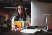 Бізнес-леді читання книги на її столі в офісі — стокове фото
