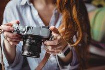 Средняя секция женщины, смотрящей на фотографии на цифровой камере дома — стоковое фото