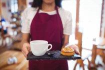 A metà sezione della cameriera che tiene una tazza di caffè e snack nel supermercato — Foto stock