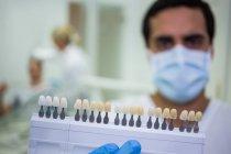 Dentiste tenant des nuances de dents dans la clinique dentaire — Photo de stock