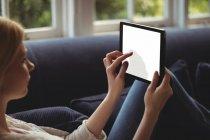 Mujer sentada en sofá con mesa digital en la sala de estar en casa - foto de stock