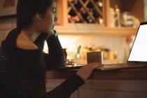 Жінка, використовуючи ноутбук кухонного столу на дому — стокове фото