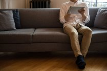 Uomo che ascolta musica su tablet digitale a casa — Foto stock