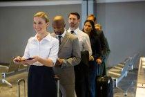 Пассажиры, стоящие в очереди у терминала аэропорта — стоковое фото