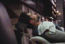 Мужчина расслабляется на стуле в парикмахерской — стоковое фото