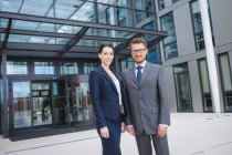 Portrait of confident businessman with colleague standing outside office building — Stock Photo