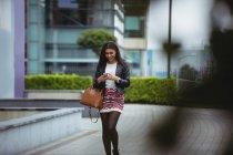 Mulher feliz usando celular enquanto caminhava nas instalações de escritório — Fotografia de Stock
