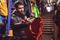 Мужчина выбирает одежду в магазине одежды — стоковое фото