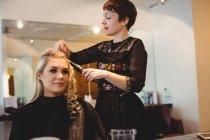 Женщина парикмахер укладки клиентов волосы в салоне — стоковое фото