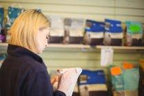 Femme écrivant sur bloc-notes dans la boutique au centre de soins pour chiens — Photo de stock