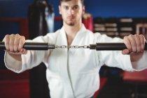 Каратист практикуется с нунчаком в фитнес-студии — стоковое фото