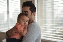 Homme moyen adulte réconfortant bébé fils à la maison — Photo de stock
