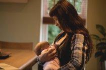 Мать кормит грудью малышку дочь на дому интерьер — стоковое фото