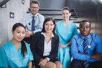 Portrait of smiling doctors and nurses sitting on staircase in hospital — Stock Photo