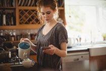 Schöne Frau mit Handy beim Zubereiten von Kaffee in der Küche zu Hause — Stockfoto