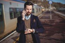 Empresário verificando o tempo ao falar no telefone celular na estação ferroviária — Fotografia de Stock