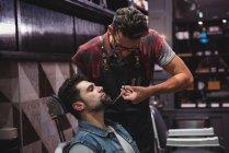 Uomo ottenere barba tagliato da barbiere con le forbici in negozio di barbiere — Foto stock