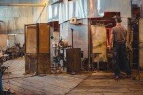 Митець опалення скла в glassblowers печі на заводі glassblowing — стокове фото