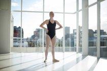 Балерина стоит с руками на талии в студии — стоковое фото