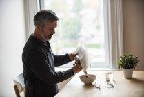 Человек наливает зерновые в миску дома — стоковое фото