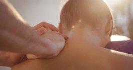 Physiotherapeut gibt einer Patientin in der Klinik eine Rückenmassage — Stockfoto