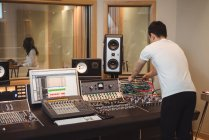 Audio engineer using sound mixer in recording studio — Stock Photo