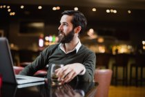 Man with glass of drink and laptop on table in bar — Stock Photo