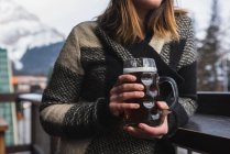 Mid section of woman in winter clothing holding beer glass in bar outdoor terrace — Stock Photo