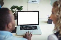Primer plano de los ejecutivos de negocios discutiendo sobre el ordenador portátil en la oficina - foto de stock