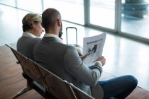 Business people reading newspaper in waiting area at airport terminal — Stock Photo
