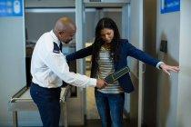 Oficial de segurança do aeroporto usando um detector de metais de mão para verificar um viajante no aeroporto — Fotografia de Stock