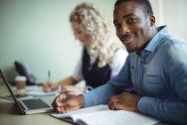 Retrato de executivos de negócios tomando notas ao usar laptop no escritório — Fotografia de Stock