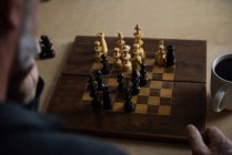 Внимательныя(ый) человек играть в шахматы на дому — стоковое фото