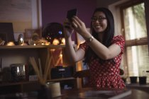 Smiling woman taking selfie on mobile phone at home — Stock Photo