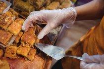 Крупный план продавщицы-женщины, занимающейся приготовлением турецких сладостей у прилавка в магазине — стоковое фото