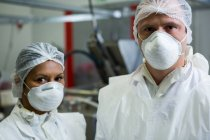 Retrato de açougueiros em máscaras cirúrgicas na fábrica de carne — Fotografia de Stock