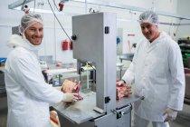 Porträt der Metzger Schneiden von rohem Fleisch auf Bandsäge Maschine Fleischfabrik — Stockfoto