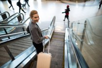 Businesswoman standing on escalator with luggage at airport — Stock Photo