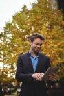 Empresário sorridente segurando celular e usando tablet digital na rua — Fotografia de Stock