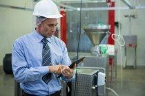 Уважний технік, використовуючи цифровий планшет на заводі м'яса — стокове фото