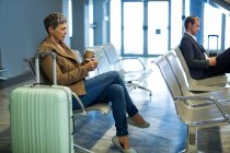 Commuter with coffee cup using mobile phone in waiting area at airport — Stock Photo