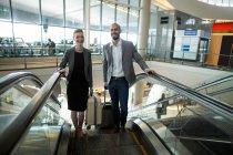 Uomini d'affari sorridenti con bagagli che salgono sulla scala mobile al terminal dell'aeroporto — Foto stock