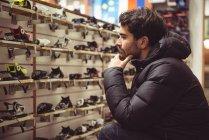 Bonito homem selecionando esqui encadernação em uma loja — Fotografia de Stock