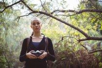 Hermosa mujer de pie con cámara en el bosque - foto de stock