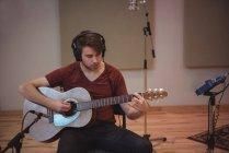 Mann spielt Gitarre im Musikstudio — Stockfoto