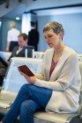 Mulher olhando para o passaporte na área de espera no terminal do aeroporto — Fotografia de Stock