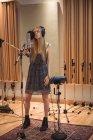 Женщина поет на микрофоне в студии звукозаписи — стоковое фото