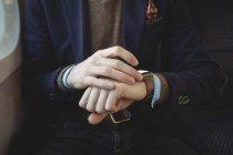Meio de seção de homem de negócios usando smartwatch enquanto viaja em trem — Fotografia de Stock
