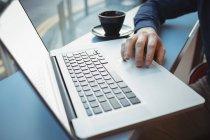 Sección media del ejecutivo masculino usando portátil en la cafetería - foto de stock
