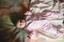 Cute baby lying on bed in bedroom at home — Stock Photo
